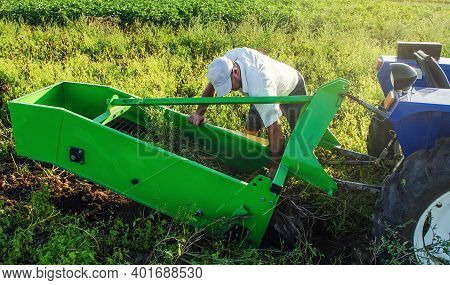 The Farmer Inspects And Repair Adjustment Of Agricultural Equipment For Digging Out Potatoes. Harves