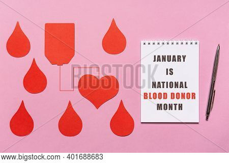 Text January Is National Blood Donor Month On White Notebook Page With Red Drops On Pink Background.
