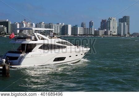 Luxury White Motor Yacht Cruising On The Florida Intra-coastal Waterway Against A Background Of Miam