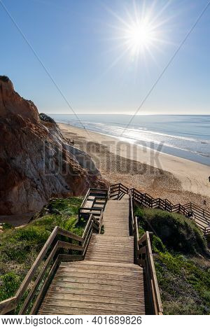 A Long Wooden Boardwalk Beach Access Leading Down To A Wide Golden Beach With Colorful Sand Cliffs