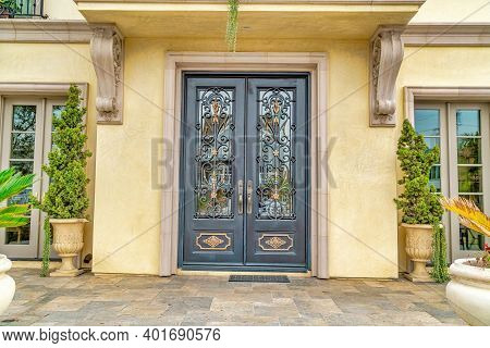 Double Door With Decorative Wrought Iron And Glass Panes At The House Entrance