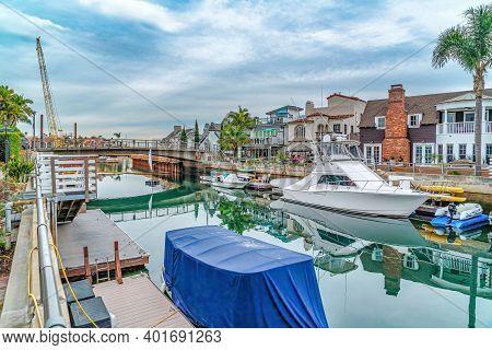 Footbridge Over Canal With Boats And Docks In Long Beach California Neighborhood