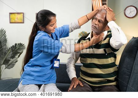 Doctor Or Physician Nurse Helping Senior Man For Neck Exercise By Rotating Patients Head At Home - C