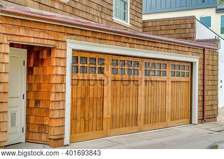 Facade Of Home In Long Beach With White Front Door And Glass Paned Garage Door