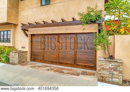 Brown Wooden Garage Door Of Home In Long Beach With Timber Frame Roof Overhang