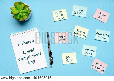 Happy World Compliment Day. Office Desk With Plant, Notebook, Pen And Paper Slips With Compliments T