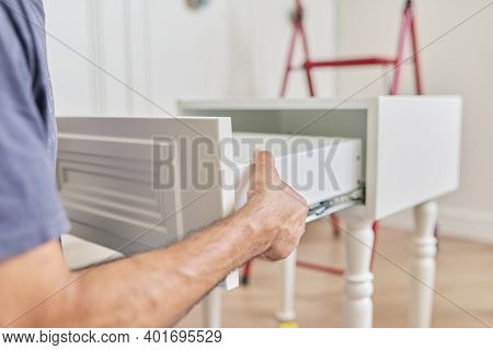 Assembly Of Wooden White Bedside Table At Home, Closeup Of A Workers Hand Making Furniture Using Pro