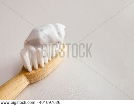Micro Plastic Particles In A Smear Of Toothpaste On A Wooden Toothbrush. Representation Of The Micro