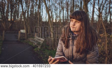 Cinematic Portrait, Person Girl Woman Standing In The Park With Mobile In Hands