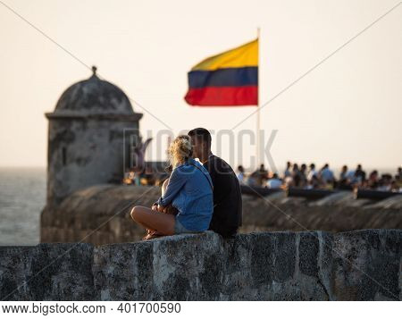 Couple Sitting On City Wall With Colombian National Flag Waving In Wind On Bastion Of Santo Domingo