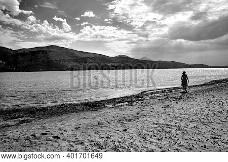 Girl In A Dress On A Sandy Beach On The Island Of Kefalonia In Greece, Monochrome Girl In A Dress On