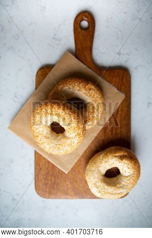 Bagels With Sesame Seeds On A Cutting Board On A Marble Kitchen Counter, Top View.