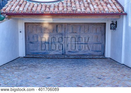 Red Tile Roof Overhang Above The Wooden Door Of Attached Garage Of A House