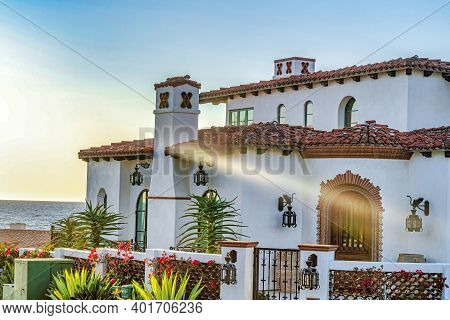 White Home With Porch And Arched Windows Against Ocean And Sky In San Diego Ca