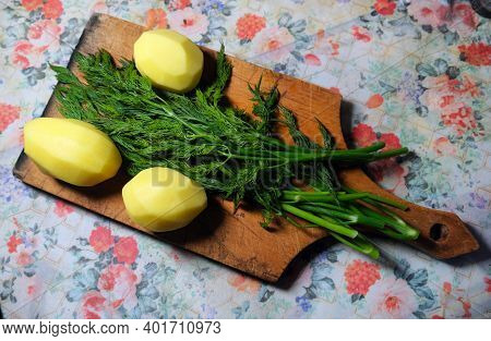 Green Dill And Peeled Uncooked Potatoes Lie On A Wooden Cut Board On A Table With A Flowered Tablecl
