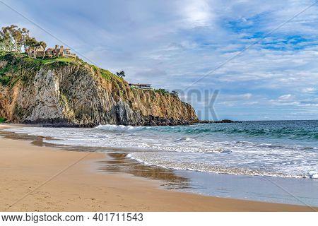 Shore And Ocean By A Rocky Cliff Against Cloudy Sky In Laguna Beach California
