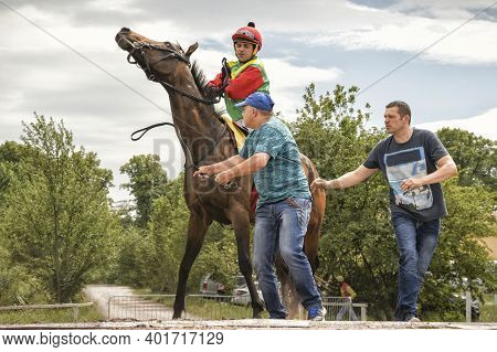 Magdeburg, Germany - 24 June 2017: Jockey Rides On A Horse To The Hippodrome. Two Assistants Help Hi