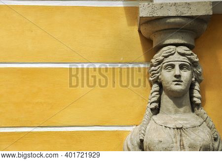 High-relief Face Of An Antique Woman Against A Yellow Wall.
