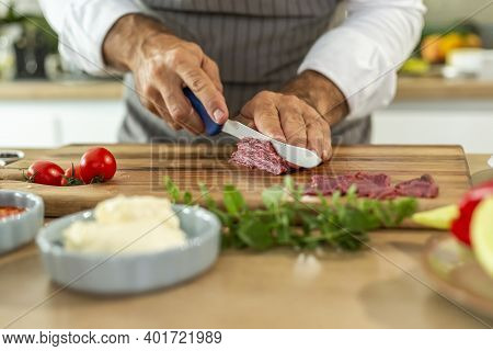 A Close-up Of The Chef's Hands Cutting Carpaccio Meat Into Thin Pieces During The Preparation Phase