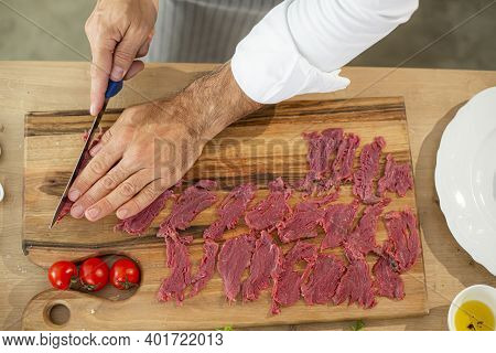 A Close-up Of The Chef's Hands Cutting Carpaccio Meat Photographed From Above, During The Preparatio