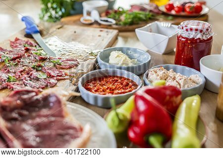 Close-up Display On A Wooden Kitchen Board Of Ready-made Carpaccio Meat For Tasting. Various Vegetab