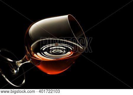 Glass Of Brandy With Flying Drop And Circle Ripple On Black Background