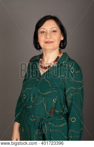 Portrait Of A Beautiful Middle Aged Caucasian Woman Wearing Green Shirt, Posing In Front Of Grey Bac