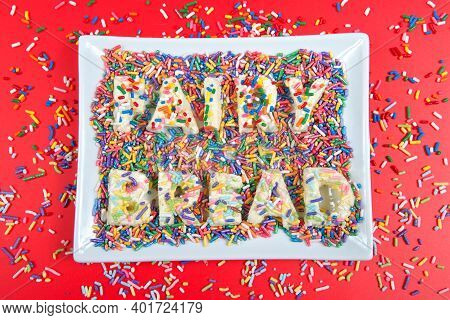 Fairy Bread Spelled With Fairy Bread On Rectangular Plate, Bright Red Background With Candy Sprinkle