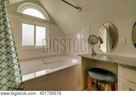 Marble Vanity Unit With Stool And Oval Mirror Beside Built In Bathroom Bathtub