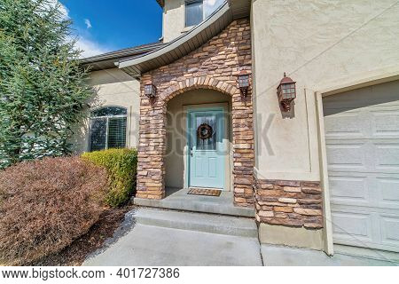 Home With Arched Stone Exterior Entryway And Glass Paned Front Door With Wreath