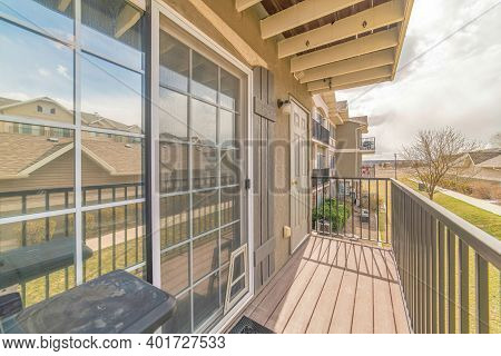 Window With Shutters And Gray Door At The Balcony Of Home With Roof Overhang
