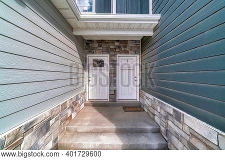 Townhouse With Stepd Leading To Side By Side Front Doors Against Stone Wall