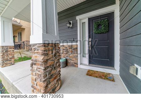 Home Facade With Open Porch And Gray Front Door Decorated With Green Wreath