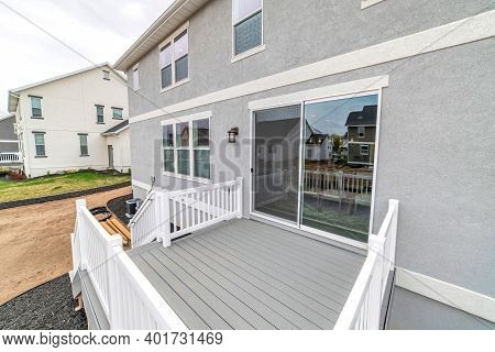 Deck Of Two Storey House With Sliding Glass Door And Stairs Leading To Yard