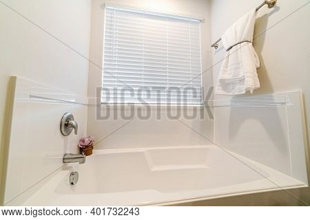Built In Shiny Bathtub Inside Clean Bathroom Of Home With White Interior Wall