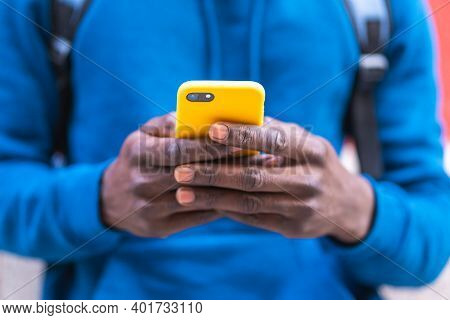 Close Up Of Black Man Using Cellphone Wearing Blue Sweater Outdoors.