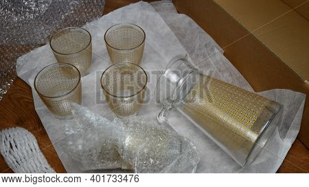 Pack Up Fragile Glassware Into Wrapping Bubble Plastic For Moving Day. Packing Up Jug And Drink Glas