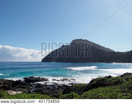 Wave Break At Makapuu Beach With Lighthouse In The Distance On Mountain Cliff In The Distance On A N