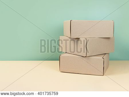 Stack Of Brown Cardboard Boxes On Mint Background. Blank Carton Box. Gifts Packaging Concept. Craft
