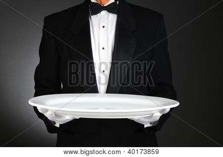 Waiter holding a large white platter over a light to dark gray background. Horizontal format, man is unrecognizable.