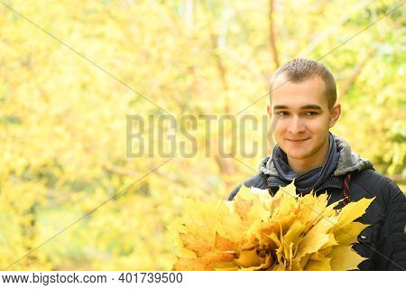 A Man Holds A Bouquet Of Autumn Leaves In His Hand. Warm Autumn Day, Yellow Autumn Leaves. Autumn Co