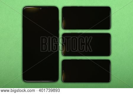 Black Mobile Smartphone With Blank Screen. Isolated On Green Background. High Resolution Photo. Full