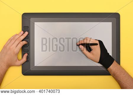 Man Hands Works On Graphic Monitor On Yellow Color Table. Black Tablet Computer With Blank Screen. H