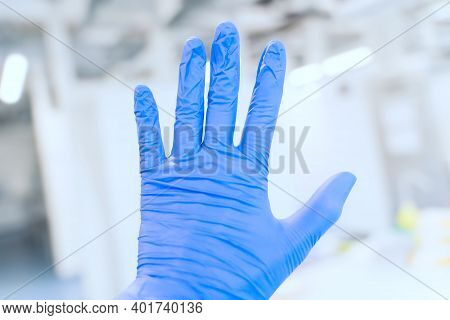 Hand With Blue Protective Nitride Gloves On Laboratory Background. Covid-19 Concept.