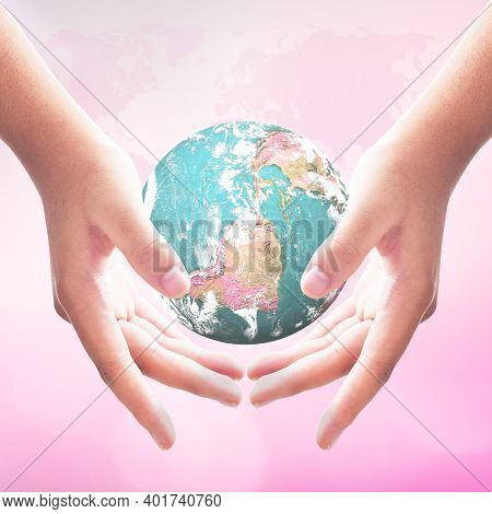 International Human Rights Day Concept: Woman Hands Holding Earth Globe Over Blurred Pink World Map