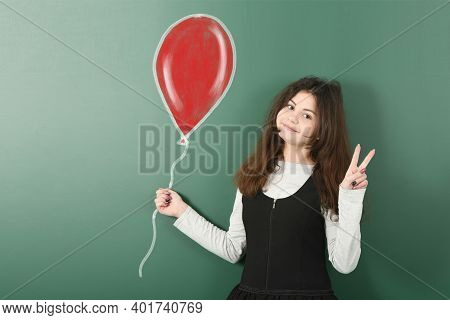 Portrait Of Pre-adolescent Child Is Holding Red Painted Balloon. High Resolution Photo. Full Depth O