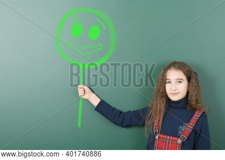 Pre-adolescent Girl Holding Painted Tablet With A Smiling Face. On School Board Background. High Res