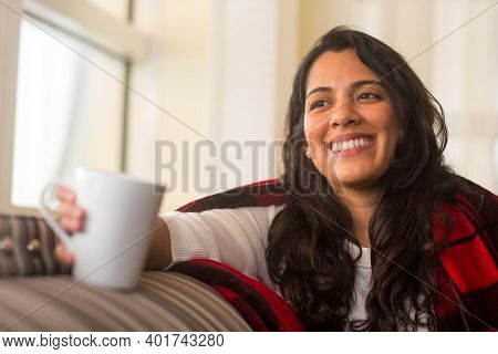 Portrait Of A Hispanic Woman Wrapped In A Cozy Blanket.