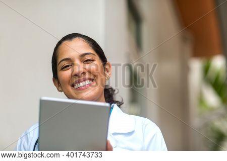 Happy Hispanic Medial Provider At Work Stock Photo.