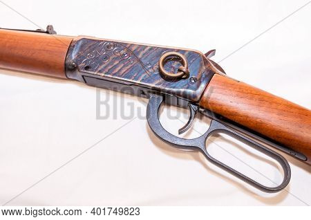 A Lever Action 30-30 Caliber Hunting Rifle With A Saddle Ring Attached On A White Background